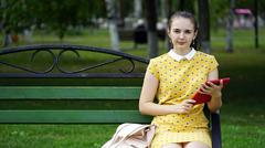 Woman sitting a bench and use the application on your tablet Stock Photos