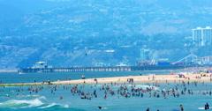 People swim in the Pacific Ocean in Santa Monica Beach in Los Angeles, 4K, RAW - stock footage