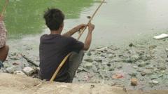 Man Fishing in Heavily Polluted Lake Water in Mandalay Burma (Myanmar) Stock Footage