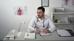 Thinking out loud. Thoughtful young bearded doctor in medical cabinet Stock Footage