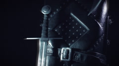 Dark Armor Glow   tracking shot of Medieval studded leather armor with sword Stock Footage