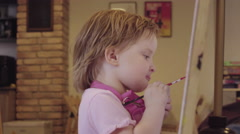 The little girl paints on a canvas, leaving and waiting for approval Stock Footage