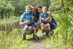 Family of four have fun in the forest Stock Photos