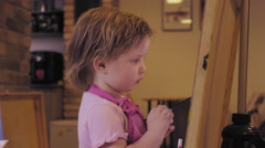 The little girl paints on a canvas in the studio and smiling Stock Footage