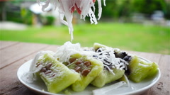 Putting finishing touch fuzz coconut on dessert glutinous rice in slow motion Stock Footage