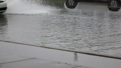 Extreme weather slo mo compact car drives through flooded street Stock Footage