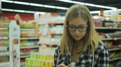 Young woman checking to do list on smartphone in grocery store with child Stock Footage