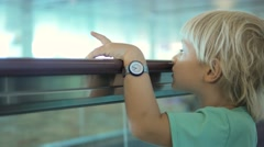 Close up of little child watching around on travelator in international airport Stock Footage