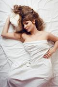 Pretty blond woman laying in bed on white shits, sexy look romantic Stock Photos