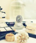 Jewelry table with lot of girl stuff on it, little mess in cosmetic brushes - stock photo