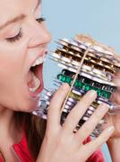 Woman taking eating pills tablets. Drug addict. - stock photo