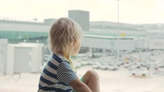 Cute child looking out the window in airport and pointing at ground staff Stock Footage