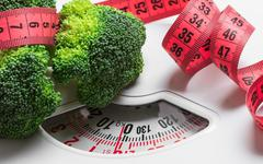 Broccoli with measuring tape on weight scale. Dieting Stock Photos