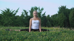 Young girl in shirt performs exercise incline on the hill with green grass Stock Footage