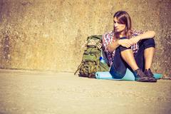 Man tourist backpacker sitting by grunge wall outdoor Stock Photos