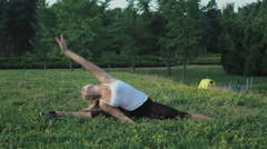Young slender blonde in shirt performs exercise incline on the hill with green Stock Footage