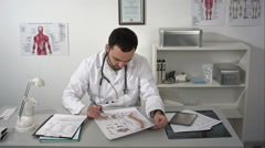Physiotherapist in his practice, the vertebral column poster on his desk Stock Footage