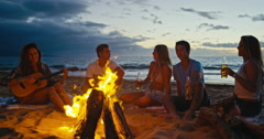 Friends Relaxing at Bonfire Beach Party Stock Footage