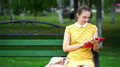 Woman sitting on a bench in the park and use the application on your tablet Stock Footage