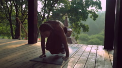 A man practices yoga on a wooden platform Stock Footage