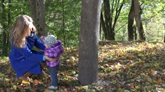 Mother embrace hug her baby daughter near tree trunk in autumn season park. 4K Stock Footage