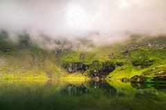 Mirroring lake on the mountain fog.Useful as background. Stock Photos