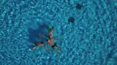 3 young men swimmers perform star figure synchronized swimming in blue pool Stock Footage