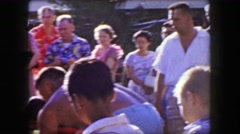 1958: Hawaiian hotel guests in aloha wear crowd watching luau. HONOLULU, HAWAII Stock Footage