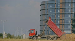 Dump truck unloading soil at construction site Stock Footage