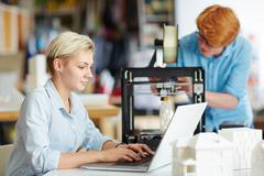 Young designer networking on background of her colleague printing architectural  Stock Photos