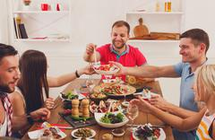 People say cheers clink glasses at festive table dinner party Stock Photos