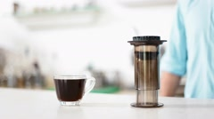 Coffee in a cup waits to be consumed next to the coffee apparatus Stock Footage