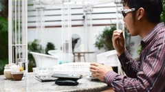 Man has a sip of tea and a bite of biscuit before attending to phone Stock Footage