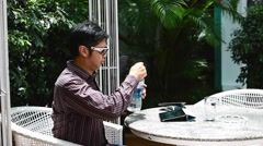 Asian man with sunglasses has a sip of water before using tablet Stock Footage