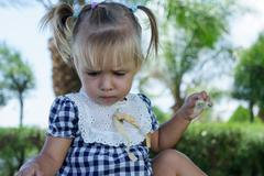 Cute little girl with straight face in summer day Stock Photos