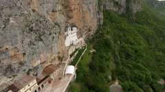 Aerial camera review of upper Serbian Orthodox monastery of Ostrog and valley Stock Footage