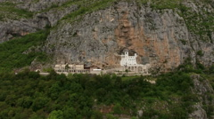 Camera flying toward to front of monastery of Ostrog in rock of Ostroska Greda Stock Footage
