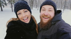 Funny woman and a bearded man doing selfie winter in snow, falling snowflakes Stock Footage