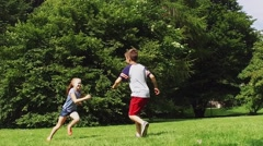 Happy kids running and playing tag game outdoors Stock Footage