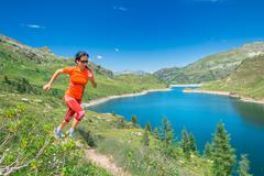 Woman runs in mountain path above a beautiful alpine lake Stock Photos