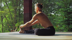 Man on a wooden platform in the park yoga Stock Footage