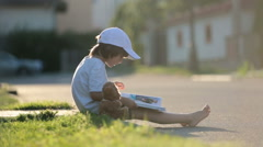 Beautiful kid boy, reading a book on the street, sitting down with teddy bear - stock footage