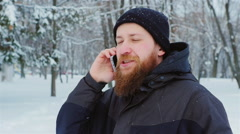 Attractive young bearded man talking on the phone. It goes in the winter park Stock Footage