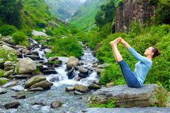 Woman doing Ashtanga Vinyasa Yoga asana outdoors Stock Photos
