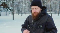 Steadicam shot: Attractive bearded man walking in a winter park, enjoys a tablet Stock Footage
