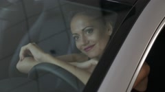 Attractive model in lingerie sitting in the car and posing for the photograph Stock Footage