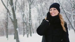 Young attractive woman talking on the phone in a winter park, smiling Stock Footage