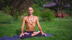 The man on the grass in the park yoga Stock Footage