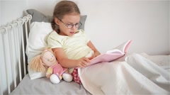 Little girl with glasses leafing through a book while lying in bed. Perhaps a - stock footage