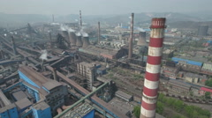 Aerial flight over massive steel factory and coal plants, pollution in China Stock Footage